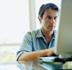 Man using computer, close-up (focus on man)